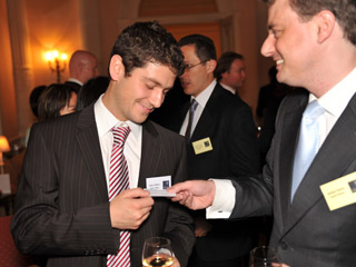Alumni trading business cards at a drinks reception