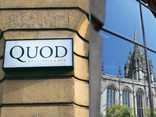 Entrance sign for Quod brasserie and bar, with University Church of St Mary the Virgin reflected in window